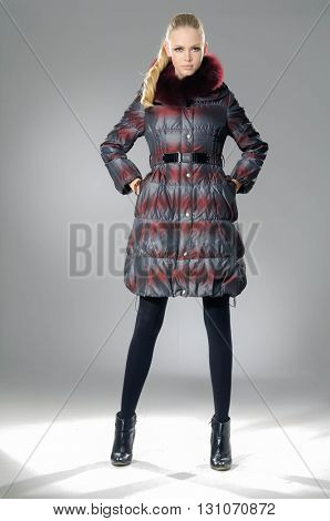 fashion model in coat clothes posing-gray background