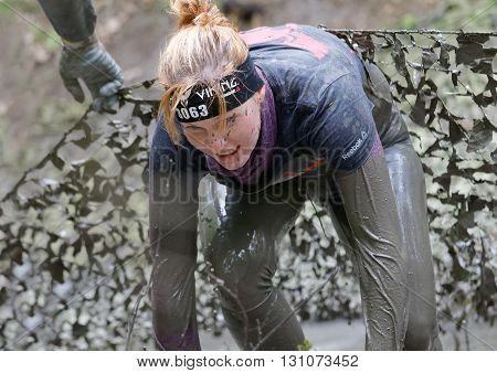 STOCKHOLM SWEDEN - MAY 14 2016: Beautiful woman with red hair covered with mud fighting to get out of a camouflage net in the obstacle race Tough Viking Event in Sweden April 14 2016