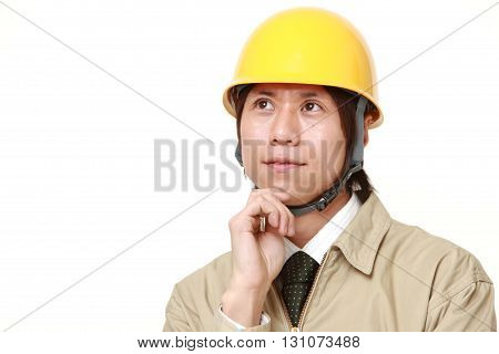 portrait of young Japanese construction worker thinks about something on white background