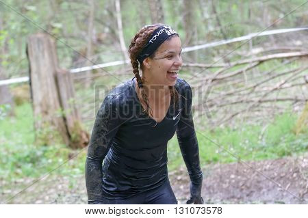 STOCKHOLM SWEDEN - MAY 14 2016: Smiling beautiful woman with braids covered with mud in the forest in the obstacle race Tough Viking Event in Sweden April 14 2016