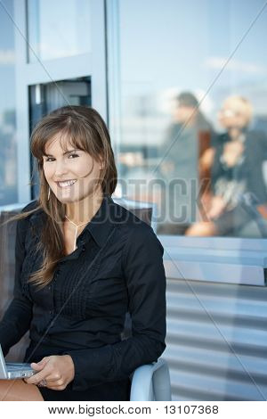 Portrait of attractive young businesswoman sitting in chair, smiling.