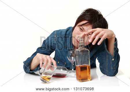 Young Japanese man in depression is drinking alcohol
