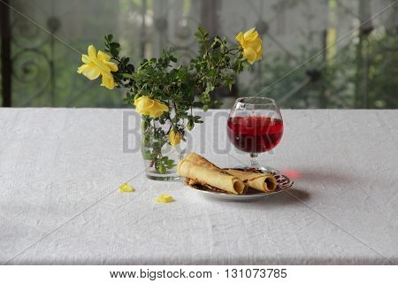 red wine in a transparent glass a bouquet of roses and wafer rolls