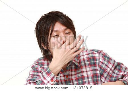 portrait of Japanese man holding his nose because of a bad smell on white background