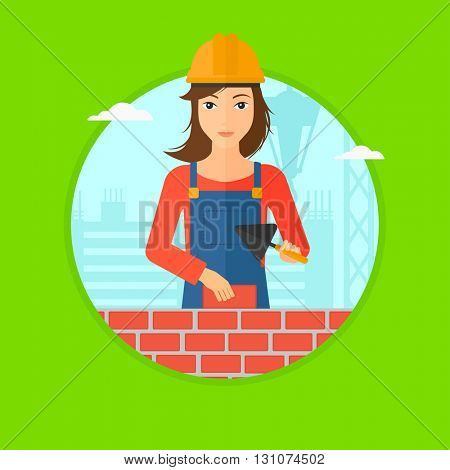 A female bricklayer in uniform and hard hat with a spatula and a brick in hands on a background of construction site. Vector flat design illustration in the circle isolated on background.