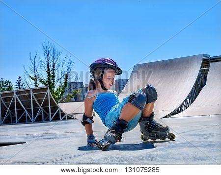 Little girl  riding on roller skates in skatepark. Girl gets up after  fall.