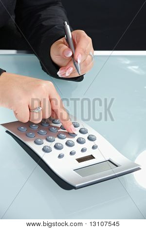 Closeup of female hands using digital calculator and holding pen.