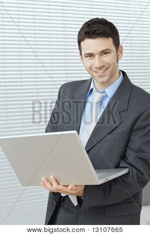 Businessman standing at office holding laptop computer in hand, working.