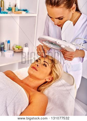 Woman middle-aged looks up in spa salon with young beautician. Tweezing eyebrow by beautician.