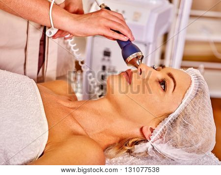 Young woman receiving electric ultrusound facial massage at beauty salon. Used for  therapy of multifunctional electroporation  device.