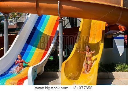 Two children on water slide at aquapark . Summer holiday. There are two water slides in aqua park. Children activities lifestyle. Children looking at camera. Outdoor.