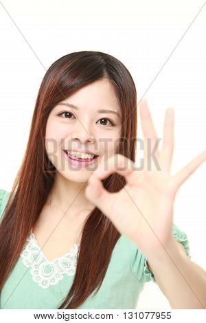portrait of young Japanese woman showing perfect sign on white background