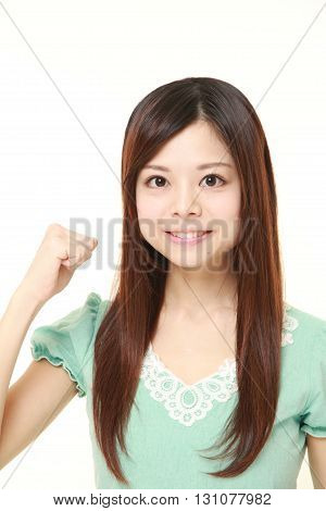 portrait of young Japanese woman in a victory pose on white background