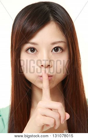 portrait of young Japanese woman whith silence gestures on white background