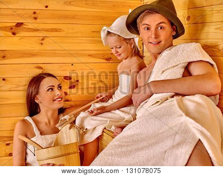 Happy family with child girl wearing in sauna hat  relaxing at sauna.