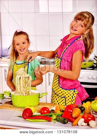 Children  eating and preparing spaghetti in pot at kitchen. Kid cooking.