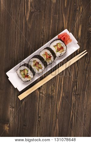 Vegetarian sushi rolls with chopsticks over brown wooden background. Top view. Space for text