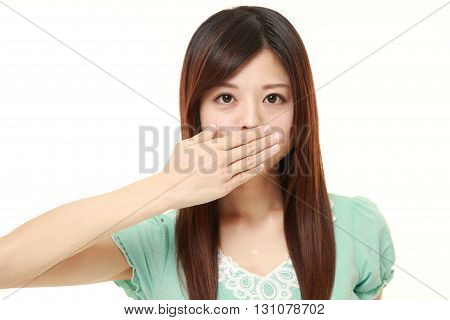 Japanese woman making the speak no evil gesture