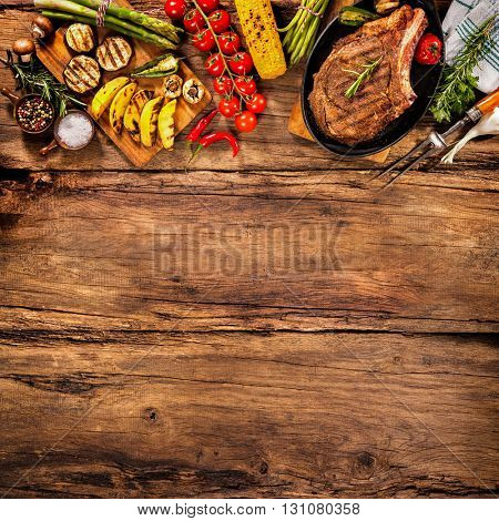 Beef steak with grilled vegetables and seasoning on wood