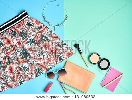 Woman hipster essentials. Fashion urban summer outfit, girl clothes set, cosmetics, makeup accessories. Stylish handbag clutch, pink dress, necklace, sunglasses. Unusual overhead, top view on blue