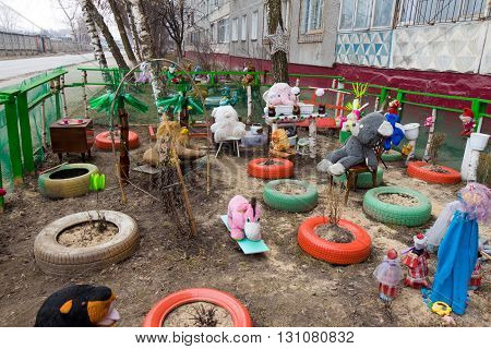 Colored toys tires and dolls around a multistory home