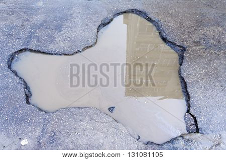 Pit on the asphalt road filled with dirty water in which the house is reflected