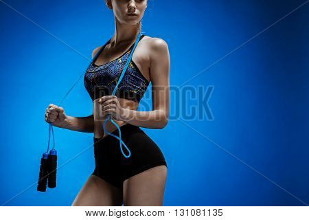 Muscular young woman athlete with a skipping rope on blue background.