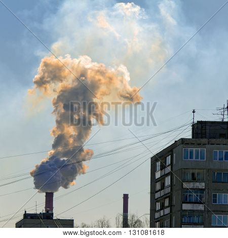 The red smoke from the chimney and houses with wires