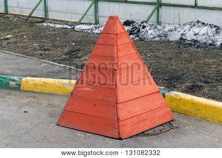 Red wooden safety cone stands on a sewer manhole