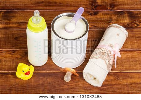 Baby milk formula feeding bottle, pacifier and towel on a background of dark wood.