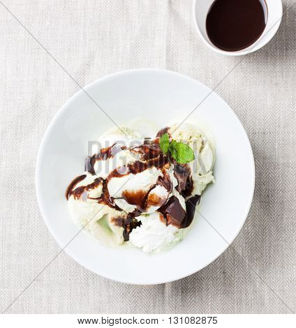 Vanilla and pistachio ice cream with chocolate sauce in a bowl on a plate on a linen textile top view