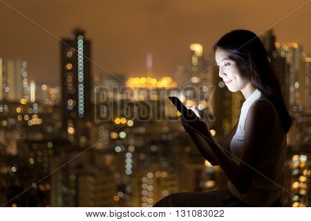 Asian Woman looking at mobile phone