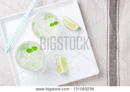Non alcohol cold mojito cocktail with fresh lime mint and crushed ice on a white plate top view closeup with place for text