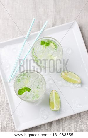 Non alcohol cold mojito cocktail with fresh lime mint and crushed ice on plate with ice a linen textile top view