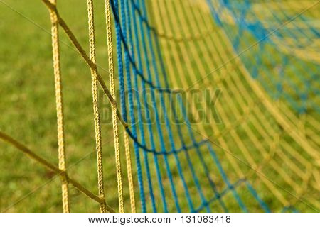 Detail Of Yellow Blue Crossed Soccer Nets, Soccer Football In Goal Net With Poor Grass On Playground