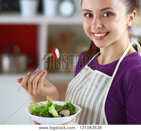 A young woman eating salad in her kitchen