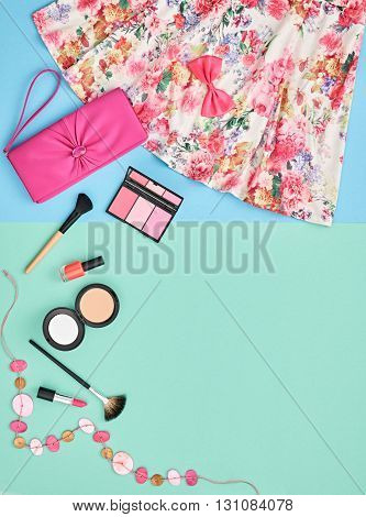 Fashion lady summer overhead outfit, girl clothes set. Cosmetics, makeup accessories. Bright woman essentials. Stylish pink handbag clutch, trendy dress, necklace. Unusual date look, top view on blue