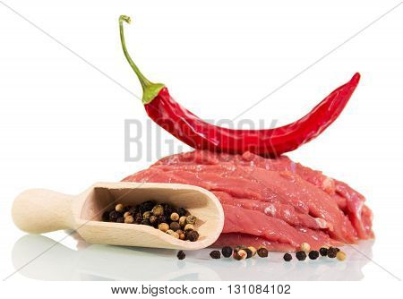 Raw meat beef, red and black pepper isolated on white background.