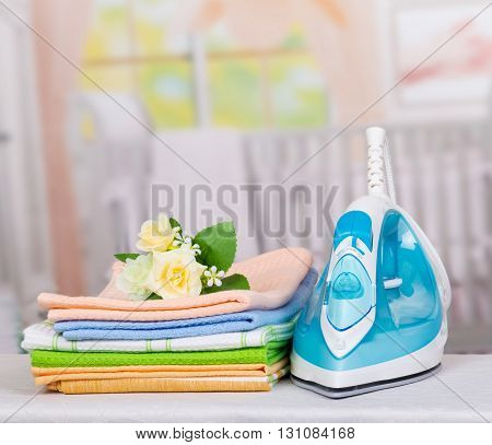 Electric iron and colorful towels on the background of the ironing room.
