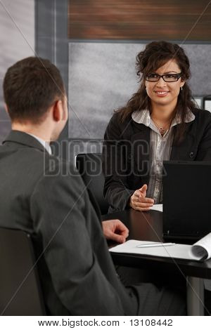 Happy young female candidate smiling to businessman during job interview.?