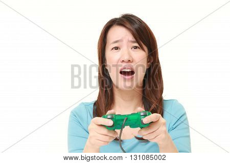 portrait of Japanese woman losing playing video game on white background