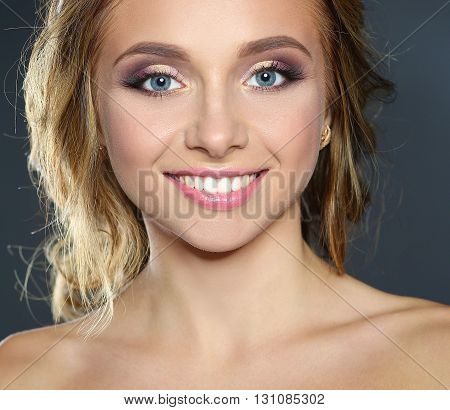Studio shot of a beautiful young woman with perfect skin against a gray background