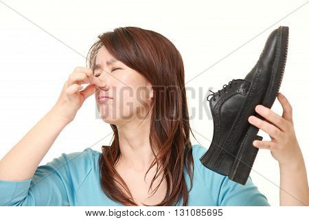 portrait of Japanese woman with smelly shoes on white background