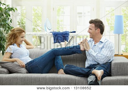 Pareja relajarse en casa en el sofá, hombre dando pie da masajes a su gildfriend.