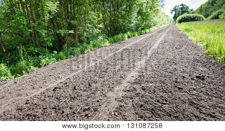 Seemingly almost endless path of loosened soil with a tire track in a rural area. It's a sunny day in the spring season.