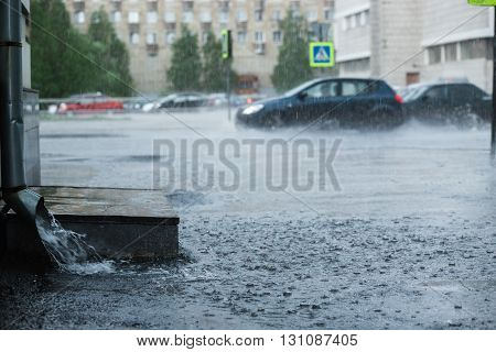 Rain water flowing from a metal downspout during a heavy rain. concept of protection against heavy rains rain flood