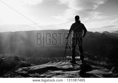 Nature Photographer With Tripod On Cliff And Thinking. Dreamy Fogy Landscape, Orange Misty Sunrise I