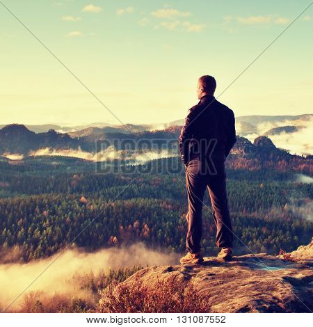 Tourist On The Cliff Of Rock In Rock Empires Park Is Watching Over The Misty And Foggy Morning Valle