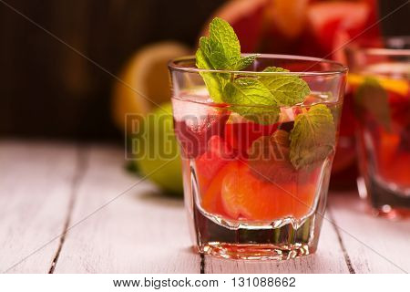 Sangria with citrus fruits, ice cubes and mint leaves in glasses over wooden background. Selective focus