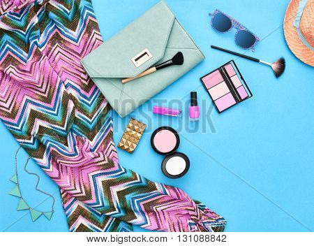 Fashion stylish clothes, cosmetics, makeup accessories set. Urban summer girl colorful outfit. Stylish handbag clutch, trendy pants, necklace sunglasses. Woman essentials. Unusual overhead, top view.